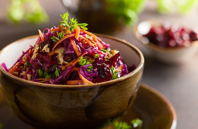 Red cabbage, carrot, apple salad with nuts and cranberry. Colesl