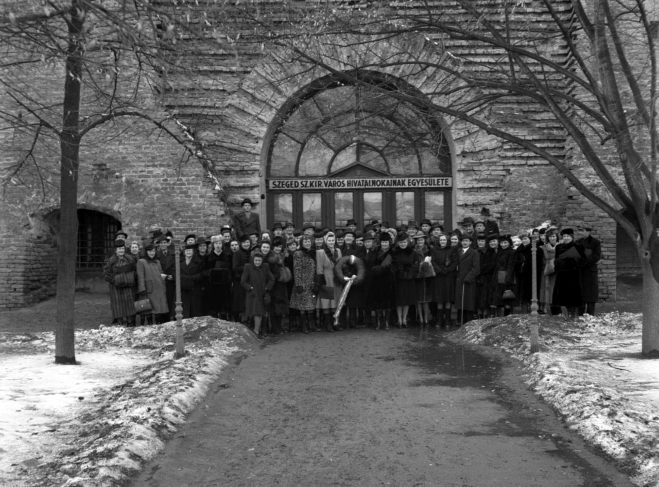Kórus koszorúval. Békások a szegedi vár előtt.A vár ma a szegedi Móra Ferenc Múzeumhoz tartozik, kiállítótér és kőtár található a jelenleg felújítás alatt álló épületben. A századfordulón halászcsárda, 1943-ban a felirat szerint Szeged sz. kir. város Hivatalnokainak Egyesülete működött itt. Hogy vajon hová került a koszorú, nem tudhatjuk, de talán Dankó Pista közelben álló szobrára, amely 1912 óta áll a cigányzenész szülővárosában. Szeged a Trianon utáni Magyarország kultikus helye lett, 1919-ben innen indult egy gondolat és Horthy Miklós is. A harmincas évekre Klebelsberg csinált belőle kultúrvárost, amely Bácska visszacsatolásával újabb feladatokat kapott: a Délvidék kultúrcentruma lett.