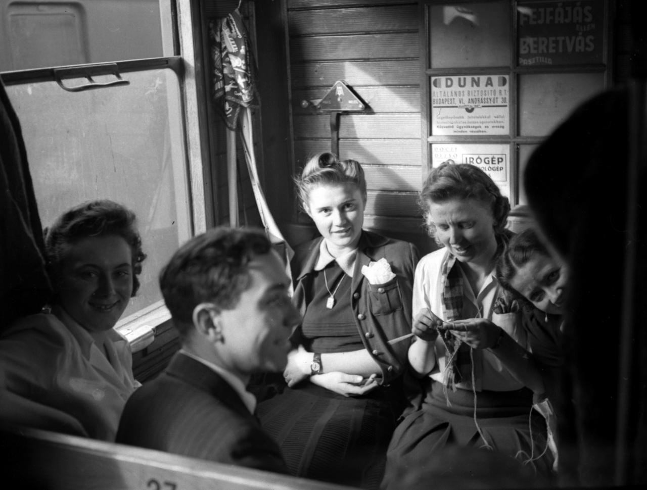 """Fejfájás ellen Beretvás-pasztilla, minden másra Duna Általános Biztosító. Életmegoldások egy vasúti kocsiban.Lányok, fiatal nők itt (jobb oldalon Borsy Istvánné Boriska, szoprán), apjuk, bátyjuk, férjük, szerelmük az orosz fronton. A 2. magyar hadseregről alig szivárognak a hírek: """"Muszka földre lassan jár a posta, [...] a halványzöldszín tábori levél""""– búgta Karády. """"Azok a kemény csapások, amelyeket a Don mentén honvédőink elviseltek, azok a nehéz szenvedések, amelyeket kiállottak és azok a példátlan teljesítmények, amelyeket kiverekedtek, arra kell, hogy ösztönözzenek bennünket, hogy a védekező fegyvert még keményebben markolva, töretlen lélekkel küzdjük végig a magyarságnak ezt a sorsdöntő küzdelmét""""– nyilatkozta éppen a fellépés napján a magyar nemzetvédelmi propagandaminiszter."""