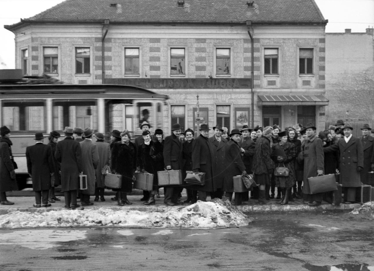 A Budapesti Kórus tagjai a szegedi Indóház téren, az 1-es villamos megállójában.1941-ben ezen a környéken esett az egyik első háborús bomba Magyarországra. Pár nappal azelőtt, hogy megkezdődött a Délvidék visszacsatolása, a jugoszláv légierő bombázói jelentek meg a légtérben, célpontjuk a szegedi vasútállomás és a vasúti híd volt. A légvédelem a támadó kötelék összes gépét megsemmisítette, szegedi halálos áldozat nem volt. A Délmagyarország akkori beszámolója szerint az állomásnak szánt bomba ugyan átszakította az épület mennyezetét, de nem robban fel: az állomásfőnök rugós díványain ide-oda pattogva végül egy párnán kötött ki, az utászok pedig ártalmatlanították.