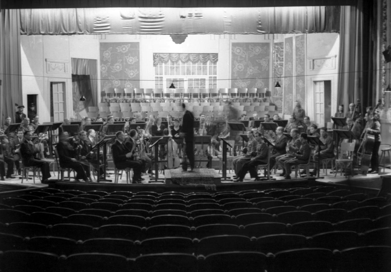 A filharmonikusok beállása a Városi Színház (ma Szegedi Nemzeti Színház) színpadán.Végül nemcsak Kodály Te Deumát és Beethoven IX. szimfóniáját adták elő, hanem Kodály Jézus és a kufárok című a cappella művét is. Két koncert volt: február elsején a diákoknak tartott főpróbahangverseny, másnap egy délelőtti koncert. A helyi filharmonikusok fiatal karnagya, Fricsay Ferenc tudatosan szoktatta zenéhez a szegedi ifjúságot, előbb a Belvárosi Moziban, majd a Városi Színházban szervezett nekik koncerteket.