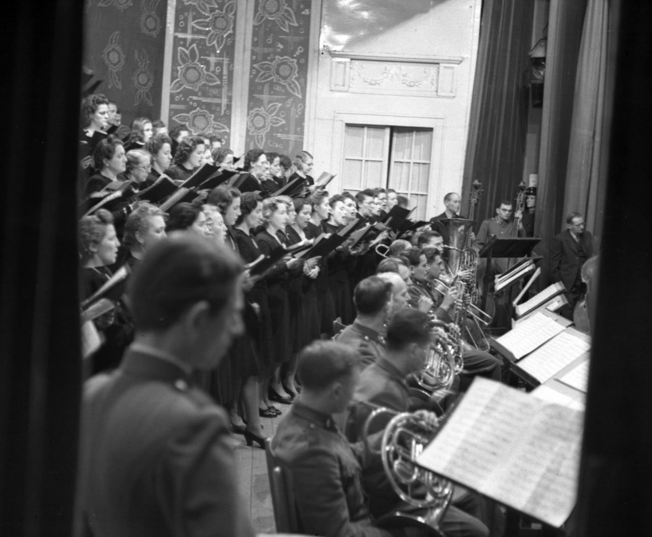 A fellépés a függöny takarásából. A kórus és a szimfonikusok a Városi Színházban.A kórus ennél izgalmasabb felállásban is szerepelt már, Bárdos ugyanis több mozdulatdrámát írt a kortárs mozdulatművészet meghatározó alakjának, a párizsi évei alatt Isadora Duncantől is inspirálódott Dienes Valériának. A hangszereket kitiltó Dienes a színpadra a mozdulat kórusát állította, Bárdosét az erkélyre.