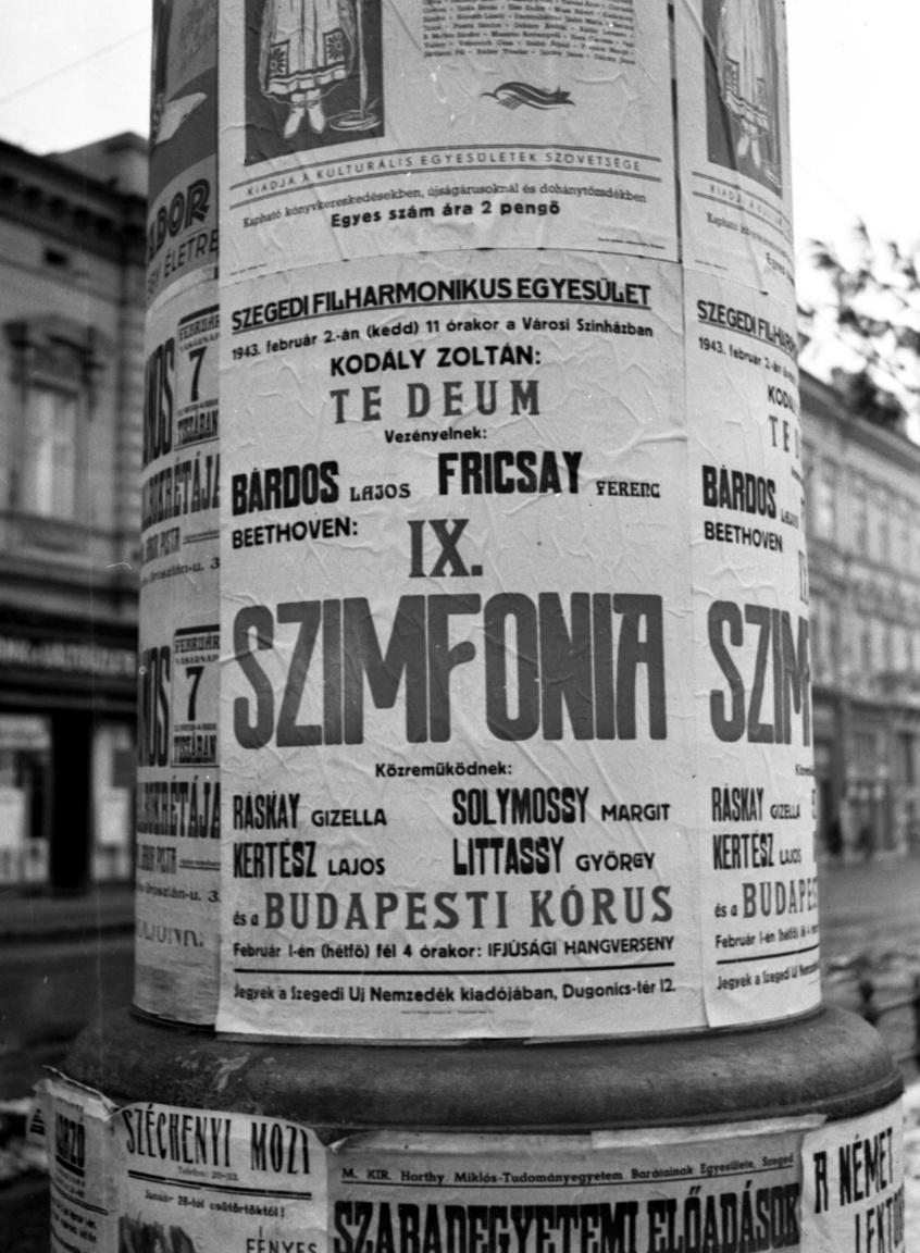 A kórus fellépését hirdető plakát a Széchenyi tér és a Híd utca sarkán, az oszlop mögött jobbra az Aigner-ház.A Fortepanon valószínűleg Lissák Tivadar hagyatékában található a legtöbb plakát; van reklám és propaganda, kézzel írt és nyomtatott falragasz, Budapestről, vidékről és a frissen visszacsatolt területekről. Az elképesztően értékes és izgalmas kortörténeti dokumentumok közül a nyilas rémuralom plakátjairól részletesen itt írtunk. Ha a bélyeggyűjtőknek különösen sokat ér egy rontott darab, a plakátgyűjtőknek ez lenne igazi kincs: Bárdos Lajos neve szerepel a szegedi filharmonikusokat vezénylő Fricsay Ferenc mellett, de mi már tudjuk, hogy őt Péter Kálmán helyettesítette. Az operaházi vendégművészek Ráskay Gizella, Solymossy Margit, Kertész Lajos és Littassy György voltak.