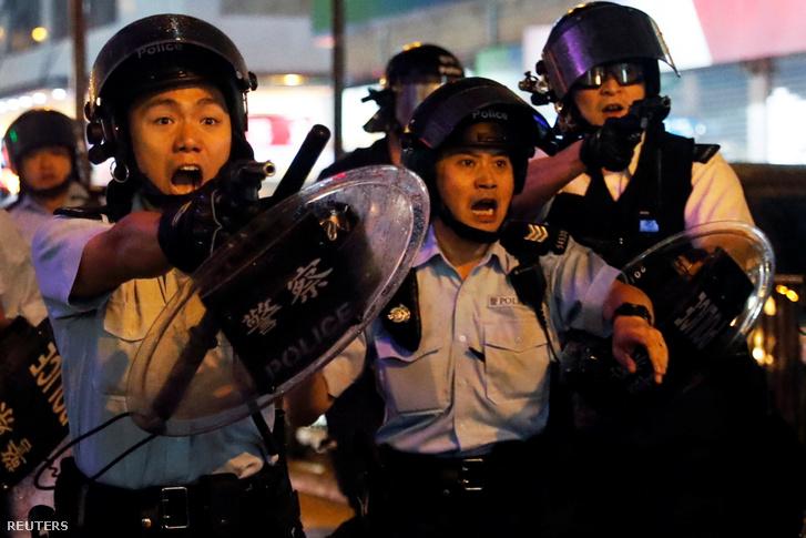Hongkongi rendőrök fegyvert fognak a tüntetékre Tsun Wanban 2019. augusztus 25-én