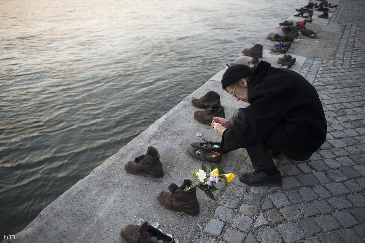 Egy résztvevő mécsest gyújt a civilek tiltakozó megemlékezésén a budapesti Cipők a Duna-parton emlékműnél 2015. március 20-án. A mintegy száztagú csoport azért gyűlt össze a Parlament közelében lévő rakpartszakaszon lévő emlékműnél, hogy tiltakozzon Kulcsár Gergely korábbi emlékműgyalázó cselekedete miatt.