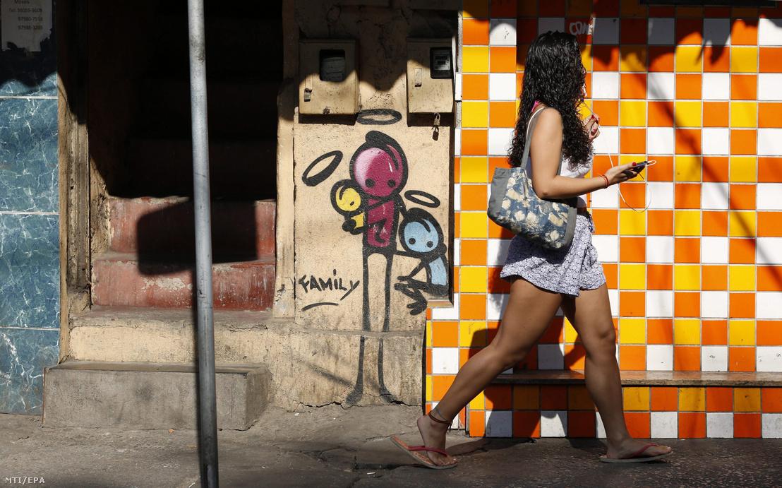 Fiatal lány sétál a Rio de Janeiró-i nyári olimpia létesítményeinek szomszédságában lévő tengerparti nyomornegyedben, a Rocinha favelában 2016. augusztus 17-én. Brazília legnagyobb szegénynegyedében több mint 120 ezer ember él alapvető higiéniai, egészségügyi és jóléti szolgáltatások nélkül.