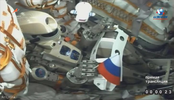 A Roszkozmosz Orosz Szövetségi Űrügynökség által közreadott, videofelvételről készített kép a FEDOR (Final Experimental Demonstration Research) nevű humanoid robotról orosz zászlóval a kezében a Szojuz MSz-14-es, pilóta nélküli űrhajó fedélzetén útban a Föld körül keringő Nemzetközi Űrállomásra 2019. augusztus 22-én, a fellövés után.