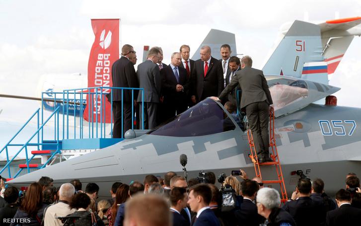 Vlagyimir Putyin orosz elnök, Denis Manturov orosz ipari és kereskedelmi miniszter és Recep Tayyip Erdogan török elnök egy Sukhoi Su-57 ötödik generációs gépét vizsgálja.