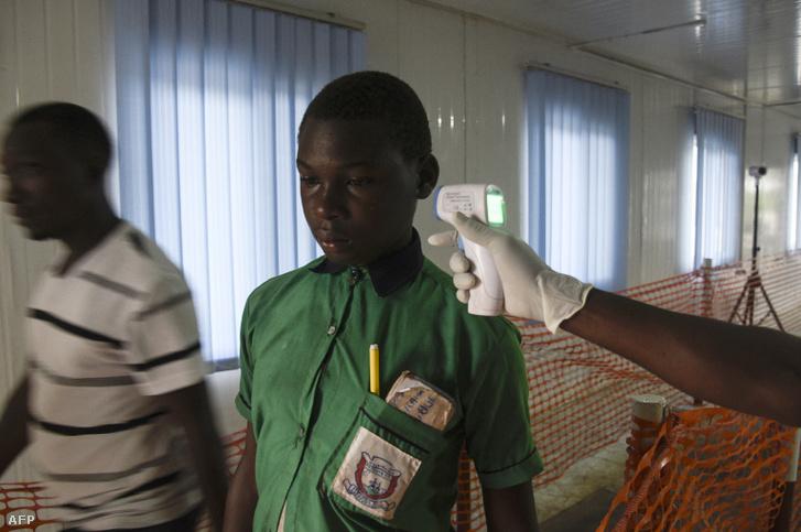 Egy egészségügyi tisztviselő ellenőrzi a Kongói Demokratikus Köztársaságból (KDK) érkező tanuló hőmérsékletét a Mpondwe határátkelőhelynél