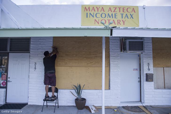 Egy üzlet tulajdonosa deszkázza be a boltja ablakait, így készül az érkező Dorian hurrikánra a floridai West Plam Beachen 2019. augusztus 30-án