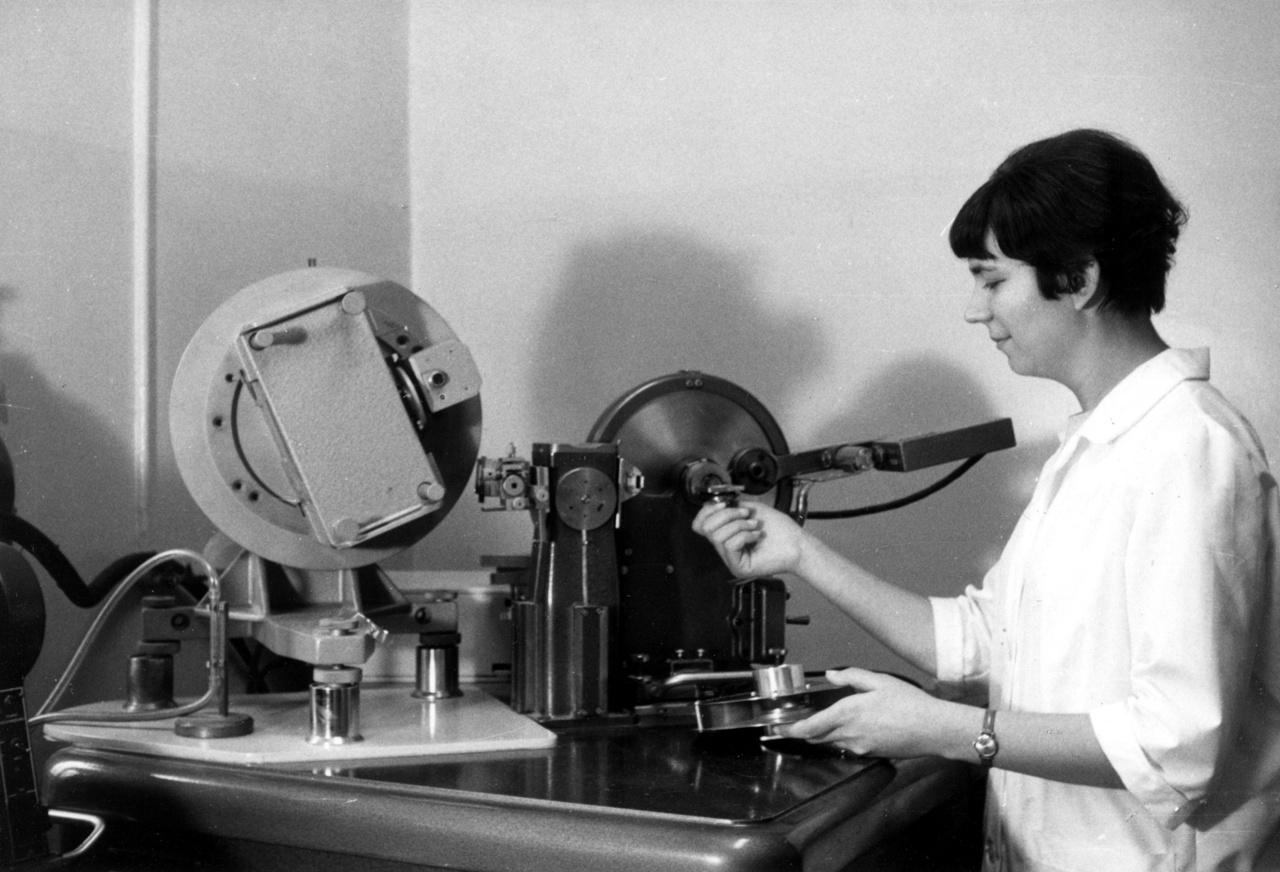 A Földtani Intézetben és utódszervezeteiben a laboratóriumok létrejötte és fejlődése, azaz a földtani anyagvizsgálati munka kibontakozása és elmélyülése párhuzamosan zajlott az intézet feladatainak változásaival, egyre sokrétűbbé válásával. A kémiai laboratórium létrejötte után nem sokkal, az agrogeológiai kutatások fellendülése vonta maga után az agrogeológiai–talajkémiai laboratórium felállítását. Ásvány–kőzettani laboratórium felállítására azonban csak jóval később jelentkezett igény. Az 1950-es, 1960-as évek nagy nyersanyagkutatási programjainak dömpingszerű, több tízezres méréseit pedig a rendszerváltás után a jóval nagyobb érzékenységet igénylő, környezetföldtanhoz kapcsolódó anyagvizsgálatok váltották fel. A képen: Énekes Ágnes mintát tesz a röntgendiffrakciós készülékbe az 1980-as években.