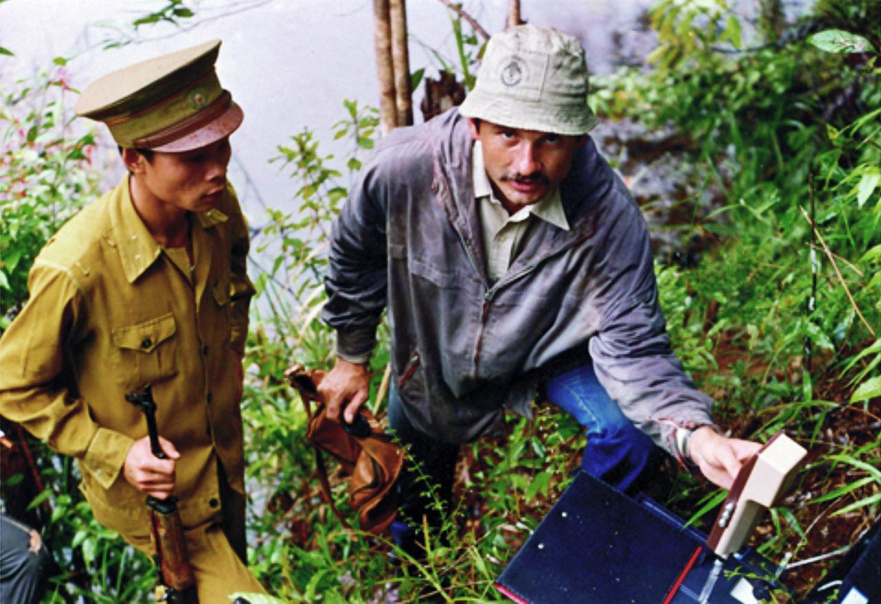 A Földtani Intézet 1985–87 között szervezett egy bauxitkutató expedíciót a dél-vietnámi Bao-Lok–Dilinh körzetben lévő Than Rai bauxit-előfordulás megkutatására. Ennek keretében egy kisebb, geológusokból és vegyészekből álló csoport utazott Vietnámba, ahol 1200 négyzetkilométernyi területen végeztek bauxitkutatást, nyersanyag-minősítő értékeléssel és készletszámítással. A terepi kiszállások itt sem zajlottak egyszerűen. A képen éppen pH-mérés zajlik, fegyveres biztosítással.