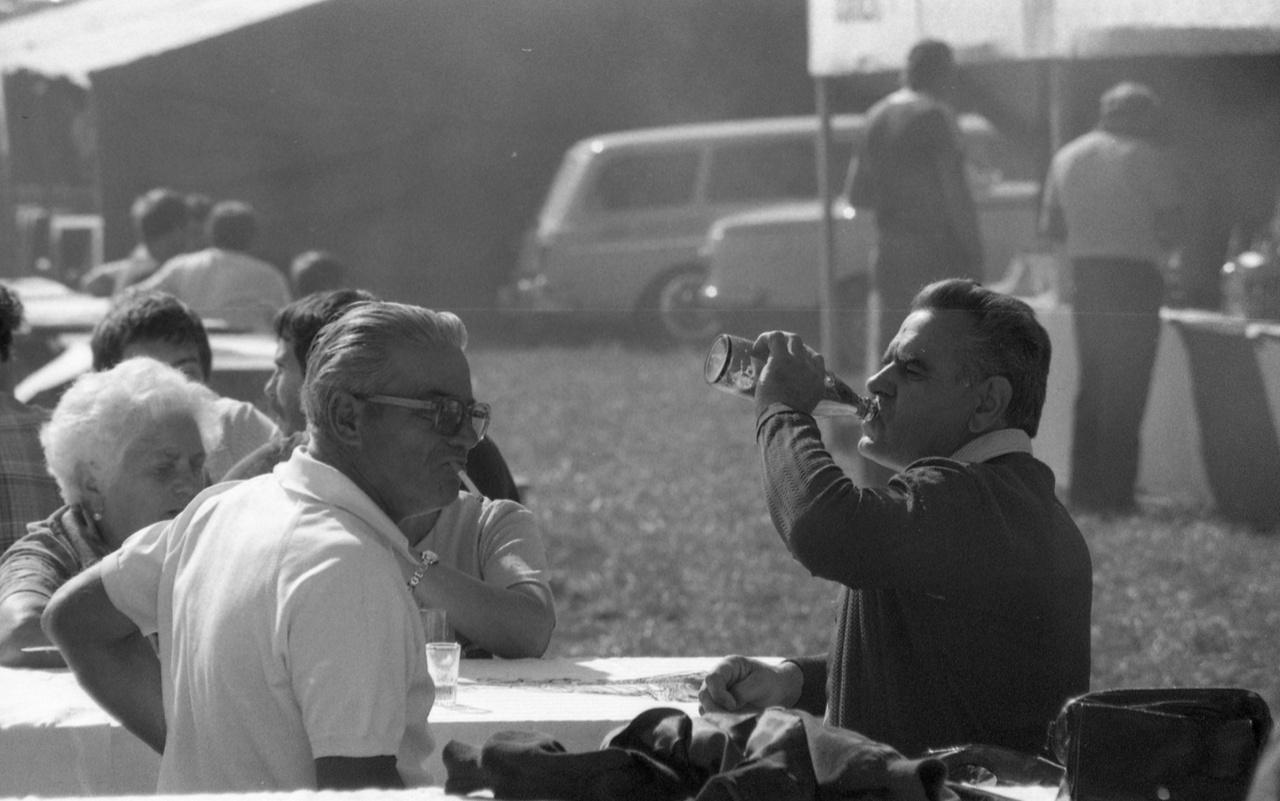 """Ópusztaszeri piknik, 1985. A település neve csak a hetvenes években kapta az """"Ó"""" előtagot, a vurstlis, vásári mutatványos, szó szerint gulyáskommunista dínom-dánom a felújított Árpád-ünnepségeken is meghatározó volt. """"A bográcsokban főtt a gulyás, és az Árpád vezérhez vagy a Galambdúchoz címzett szövetkezeti bisztróban nagy hordókból mérték a sört. Mindössze annyi változott, hogy a Zója Kozmogyemjanszkaja helyett immár Árpád nevét viselő termelőszövetkezet dolgozói nézték ámulva a vásárosok szemkápráztató mutatványait"""" - írta az ópusztaszeri ünnepségekről Kovács Ákos néprajzkutató."""