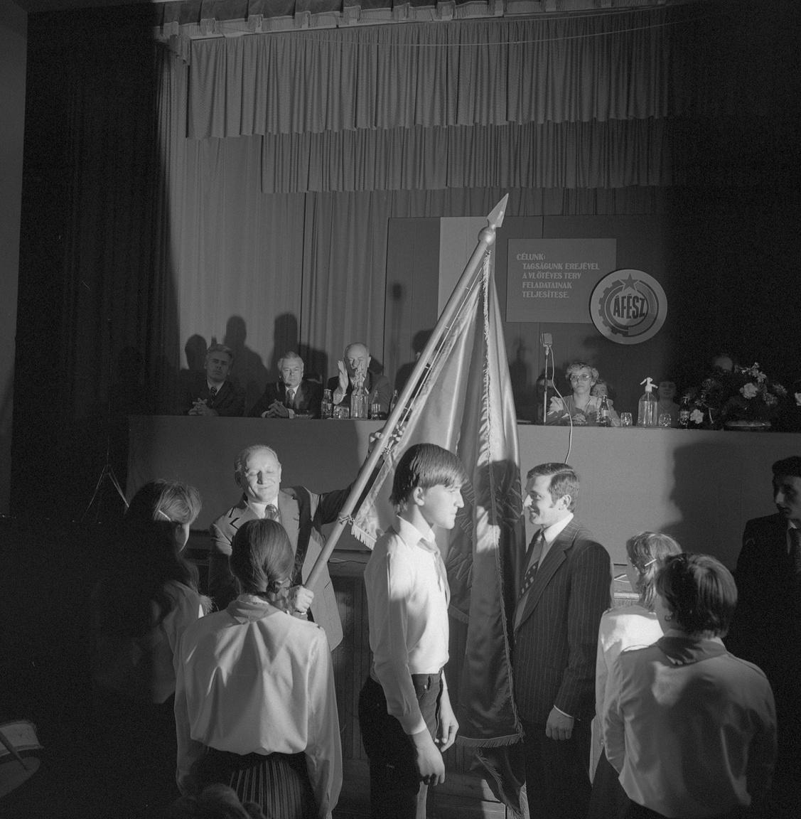 """Szövetkezeti zászlóátadás az ÁFÉSZ-ünnepségen Üllésen 1981 tavaszán. Üllés a megye egyik legszegényebb települése volt, mielőtt 1965-ben olajat találtak a határában. Ennek és a nem túl jó földeken is sikeres TSZ-nek köszönhetően építettek művházat, hidroglóbuszt, benzinkutat, és még a szomszédos Forráskutat is hozzájuk csatolták - a forráskútiak nem túl nagy örömére. A """"Csongrád megyei modell"""" jelszavával a keménykezű párttitkár Komócsin fel akarta számolni a tanyavilágot, de ez nem sikerült neki, csak a tanyaközpontok belterületét falusiasították szabályos, sakktáblaszerű utcahálózattal - mint Üllésen is."""