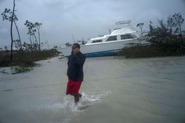Férfi telefonál egy partra vetett hajóval a háttérben a Dorian hurrikán által elpuszított területen a Bahama-szigeten fekvő Freeportban kedden.