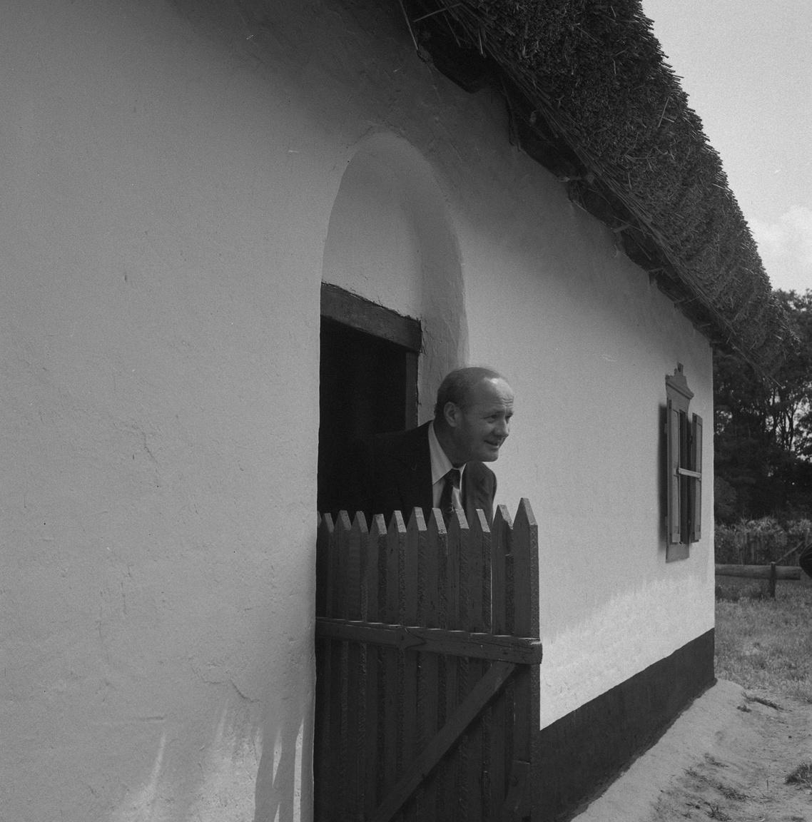 Losonczi Pál, az Elnöki Tanács elnöke kukkant ki az Ópusztaszeri Emlékpark skanzenjének egyik házikójából. Az államfő az ópusztaszeri munkás-paraszt találkozóra érkezett. Losonczi Pál tiszteletére egy 70 méter hosszú katonai sátrat vertek fel, ezt munkásőrök óvták, az egyik végében pedig a Pick hűtőkamionja fújta a hideget az illusztris vendégekre.