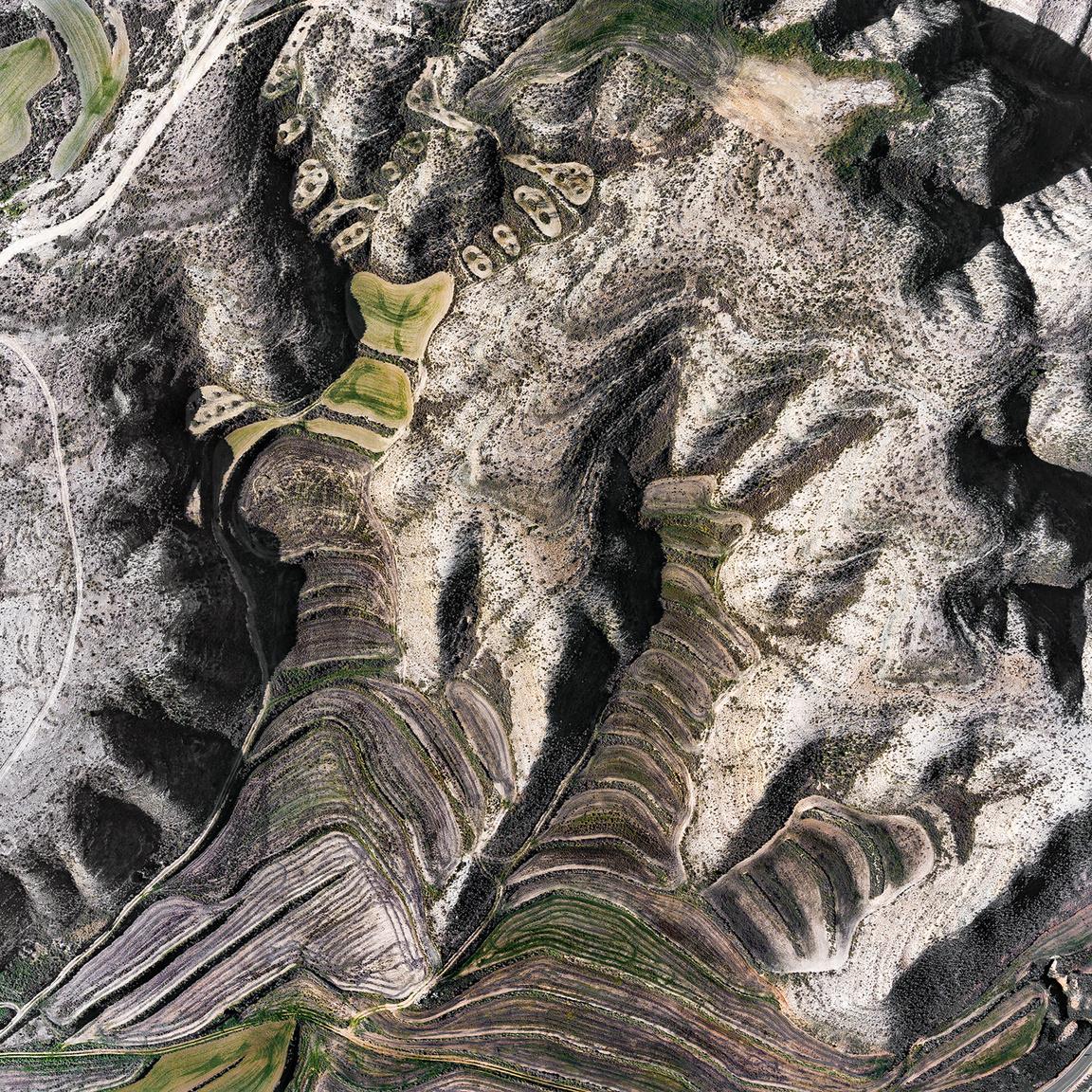 Calle ColladosDombok közti lankás területen kialakított búzamezők, ahol a dombokról lezúduló vizek hordalék formájában lerakták a termő táptalaj alapjait.Jualin, Zaragoza, Spanyolország. 2018.12.30.A képen látható terület szélessége: 640 m.