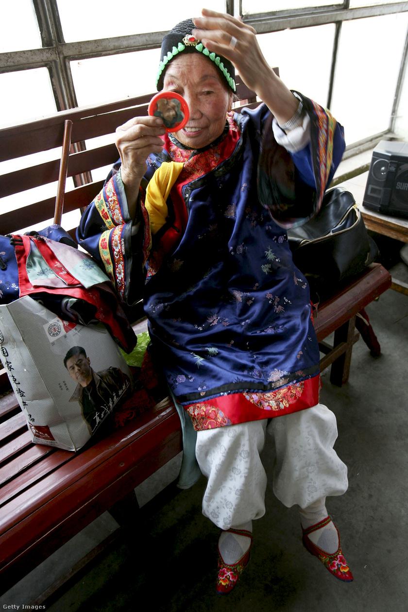 Fu Jifen már teljes díszöltözetben, éppen sminkel a fellépés előtt.