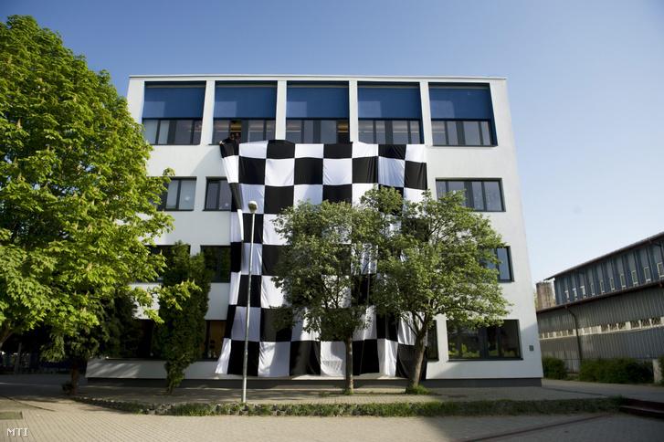 Pedagógusok egy nagyméretû kockás zászlót engednek le a Budaörsi Herman Ottó Általános Iskola ablakaiból a pedagógusok egész napos országos sztrájkjának napján 2016. április 20-án. Az iskola 62 fõs tantestületébõl 55 pedagógus vett részt a sztrájkban 678 diákjából 18 ment iskolába.