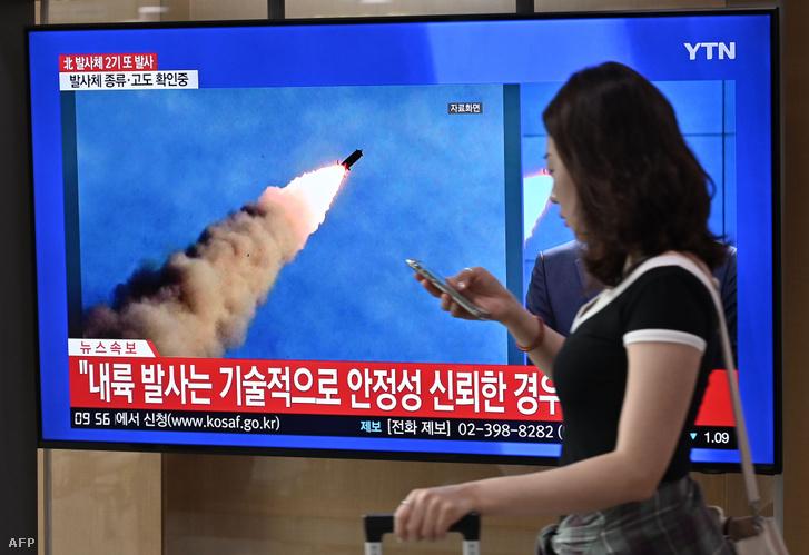 Nő sétál el az szöuli vasútállomáson egy TV mellett, ami az észak-koreai rakétakilövésról szóló hírt mutatja