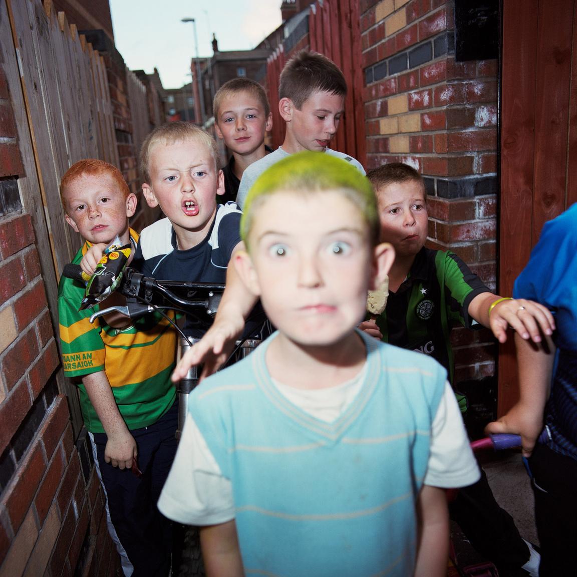 Harri Paelviranta finn fotós munkáiban az erőszak és a maszkulinitás a két fő motívum, és igyekszik ezeknek a fogalmaknak minden rétegét megvizsgálni, hiszen szinte mindenki számára mást jelentenek, annyiféleképpen lehet ezeket értelmezni. Playing Belfast sorozatával azt szerette volna bemutatni, hogyan élnek a gyerek Észak-Írország fővárosában úgy, hogy az utcai összetűzések, villongások már nem képezik a mindennapok részét. (New lodge boys #12, 2007-2010)