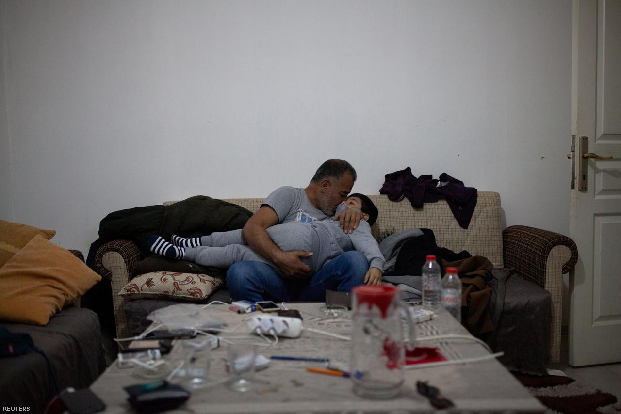 """Hanin apja az alvó fiát tartja a karjaiban, miközben a csempész hívását várják 2018. október 17-én. 20 percnyire lehettek a határtól, amikor a török parti őrség lecsapott rájuk: 3 napra börtönbe zárták őket. A család az újabb meghiúsult utazás után arról számolt be, hogy megpróbálhatják még egyszer ugyanazzal a csempésszel extra díjak nélkül.                          """"Soha nem éreztem magam rosszabbul"""" – mondja Ahmed, miközben csüggedten figyeli a sötétülő Égei-tenger fölött gyülekező felhőket. """"Annyi tervezés, és aztán jön a vihar."""""""