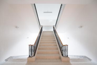 Helyreállított szocreál lépcsőház a MOME Masterben. A felfelé haladó lépcső új: stílusában követi az eredetit, de a korlátja egyszerűbb lett