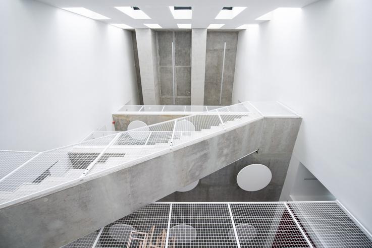 Lépcsőháznak látszó helyiség a MOME Base-ben. Valójában lifttel vagy hagyományos lépcsővel közlekedni gyorsabb, de itt kellemesebb. Ezek tulajdonképpen egymás fölé pakolt közösségi terek.A mennyezeteken megjelenő kör alakú lámpák egyúttal a tér akusztikáját is javítják