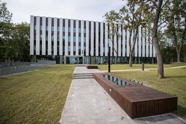 MOME Base: mintha lebegne. Az előtte látható padok üvegfelületei az épületeket összekötő, földalatti folyosók felülvilágítói
