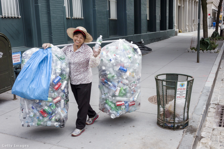 Asian woman walking with bags of recyclable plastic and metal bottles.