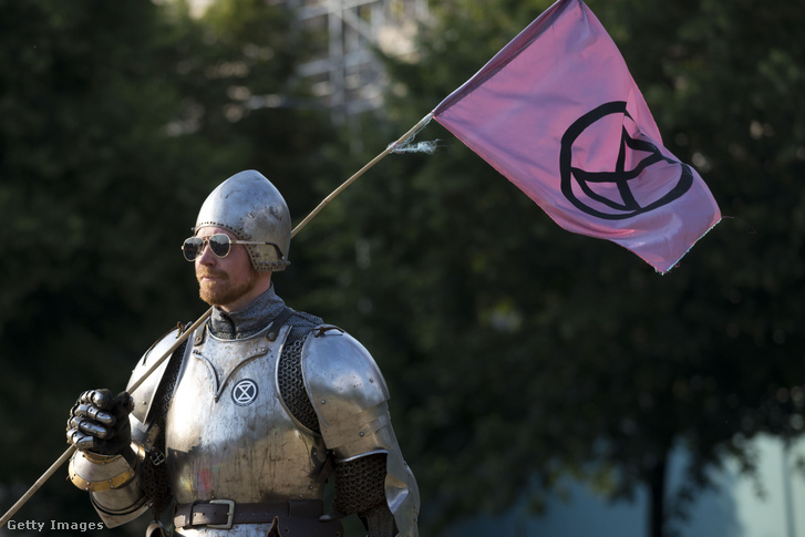 "An activist of Extinction Rebellion standing clad in armor at a demonstration for climate action called ""Project Mushroom"" in Cardiff."