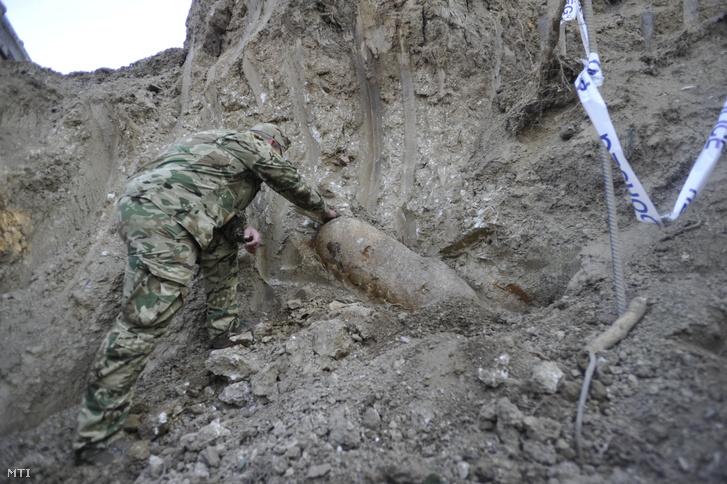 Tűzszerész egy amerikai gyártmányú, 250 kilogrammos légibombát vizsgál hatástalanítása előtt a XI. kerületi Ménesi utcában, a Szent Margit Gimnázium területén folyó építkezés területén