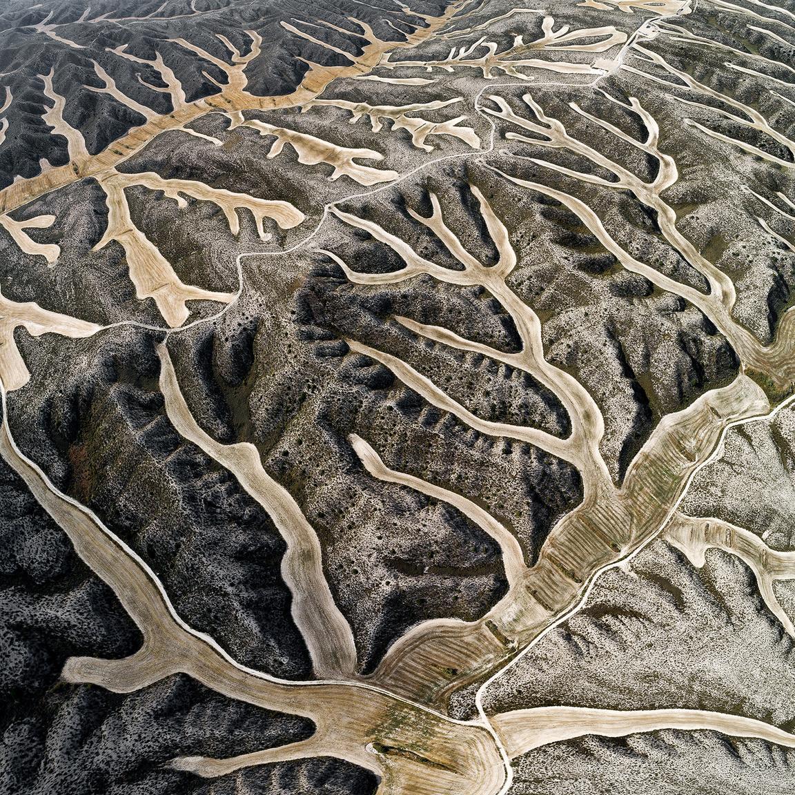 Valdemoracho #1Learatott búzamezők foltjai a dombok lankáin, ahol a talaj nedvességtartalma segíti átvészelni az ültetvényeknek a forró száraz nyári időszakot.Parque Eólico Arias, El Burgo de Ebro, Zaragoza, Spanyolország. 2018.07.14.A képen látható terület szélessége: 928 m.