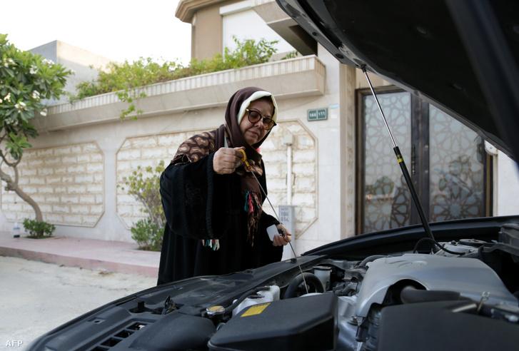 Egy 68 éves szaúdi nő ellenőrzi Lexus motorolajszintjét Qatif tengerparti városában, a fővárostól Rijádtól kb. 400 km-re keletre.