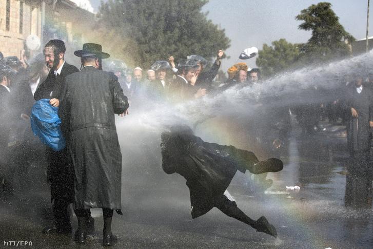 Az izraeli rendőrség vízágyúval oszlat fel tüntető ultraortodox zsidó férfiakat akik a sorkatonai szolgálat elleni tiltakozásukként eltorlaszolnak egy útkereszteződést egy sorozóiroda közelében Jeruzsálemben 2017. szeptember 17-én.