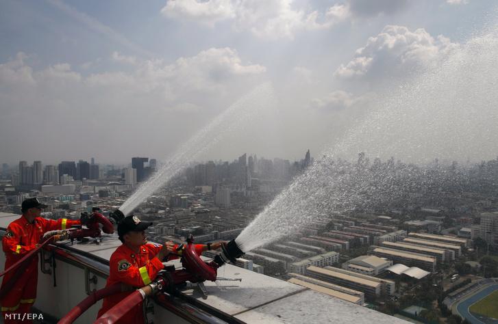 Thaiföldi alkalmazottak vízpermettel igyekeznek megkötni a levegőben szálló finomporszemcséket egy épület lapostetejérõl 2019. február 1-jén Bangkokban ahol a levegő szennyezettsége tartósan meghaladja az egészségre káros határértéket.