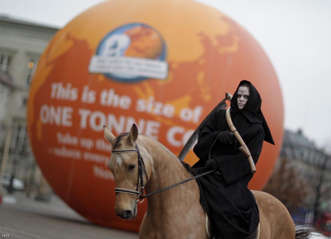 Az apokalipszis négy lovasának egyikét, a halált megszemélyesítő tüntető lovagol el egy egytonnányi szén-dioxidnak megfelelő méretű légballon mellett.