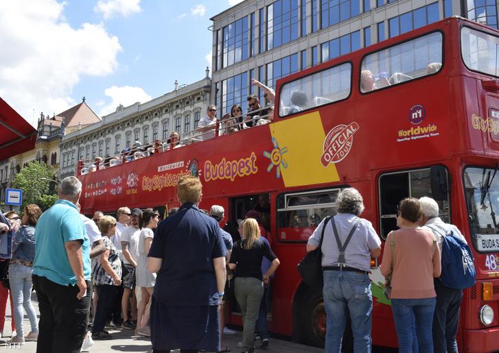 Városnéző buszra felszálló turisták Budapesten.