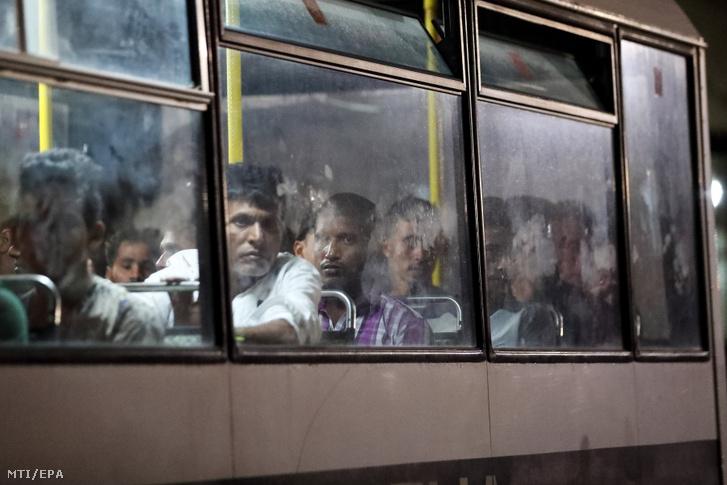 Menekültek az elszállításukat várják egy máltai rendőrségi buszon miután a máltai haditengerészet hajója a bevándorlókkal a fedélzetén kikötött a Valletta melletti Floriana Marsamxetta-öblében levõ Hay Wharf támaszponton 2019. szeptember 17-én.
