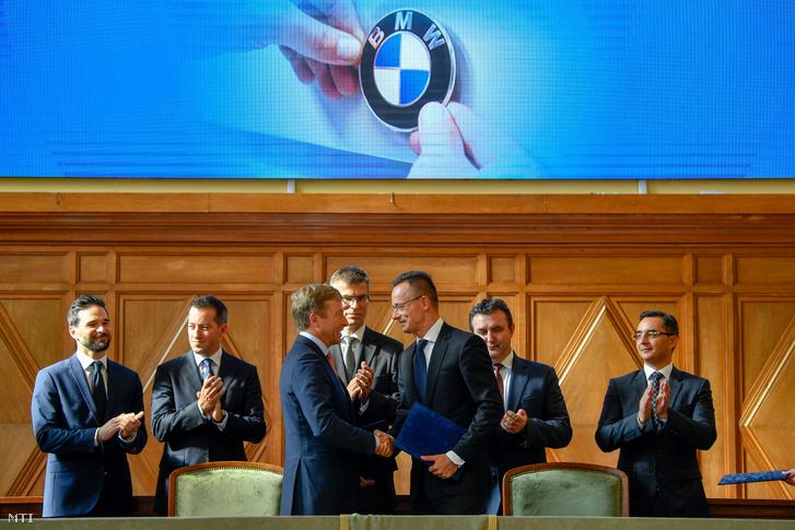 Oliver Zipse a BMW Group igazgatótanácsának gyártásért felelős tagja és Szijjártó Péter külgazdasági és külügyminiszter kezet fognak, miután aláírták a BMW debreceni gyárberuházásának támogatásáról szóló megállapodást a Debreceni Egyetemen 2018. október 12-én. Mögöttük Barcsa Lajos alpolgármester, Ésik Róbert a Nemzeti Befektetési Ügynökség elnöke, Michele Melchiorre a BMW gyár debreceni igazgatója, Palkovics László innovációs és technológiai miniszter és Papp László polgármester (b-j).