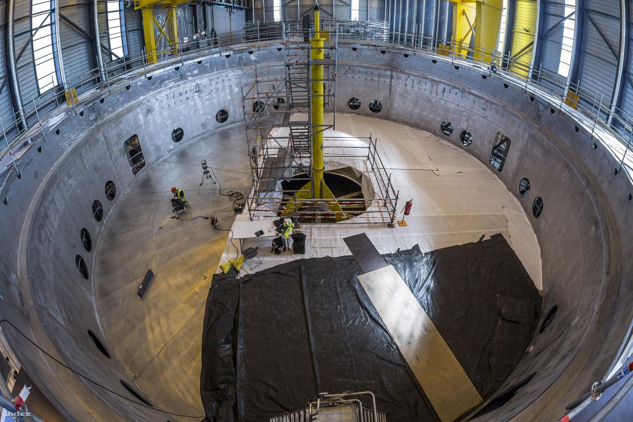 Az ITER kriosztátja egy nagyjából 30 méter magas 30 méter széles, 16 ezer köbméter űrtartalmú acélhenger lesz, ami a fúziós erőmű vákuumkamráját és az azt körülvevő szupravezető elektromágneseket foglalja majd magába, afféle termoszként. A fotón ennek a tartálynak az 1250 tonnás fenekét látni, méreteit jól szemlélteti a benne dolgozó szakember, aki különféle diagnosztikai méréseket futtatott le ottjártunkkor.