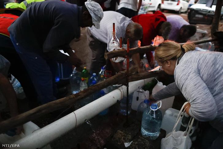 Fokvárosi lakosok ivóvizet gyűjtenek a város egyik hegyi forrásánál 2018. január 31-én.