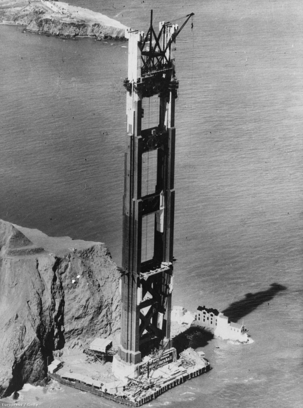 1935. Az épülőfélben lévő híd egyik pillére. Az öböl bejáratát egyébként már a híd építése előtt is Golden Gate-nek, vagyis                         aranyhídnak nevezték. A név pontos eredete nem ismert, valószínűleg az                         1850-es évek nagy kaliforniai aranylázának idején ragadt rá. Az                         eredeti neve az első erre járó spanyol telepesek nyomán Boca del                         Puerto de San Francisco volt.