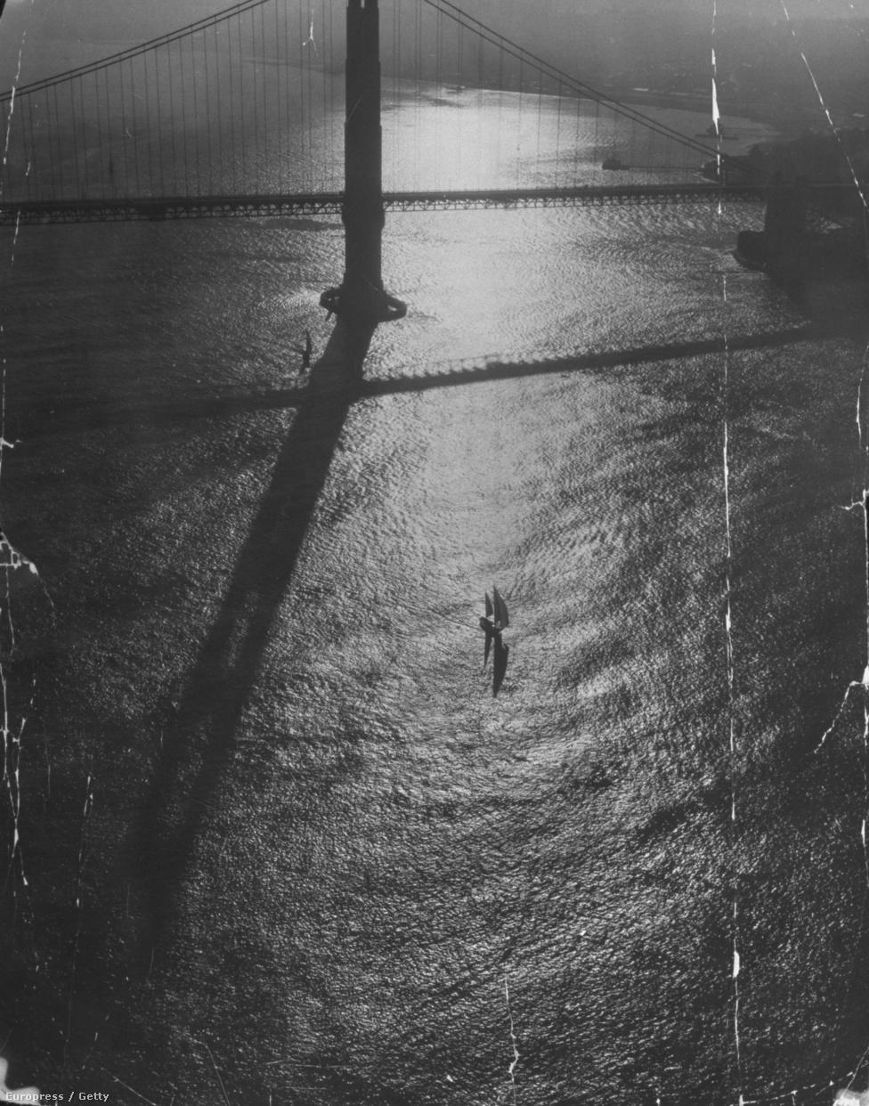 1951. A kelő nap sugarai tükröződnek a híd alatt az öböl fodrozódó vizén.