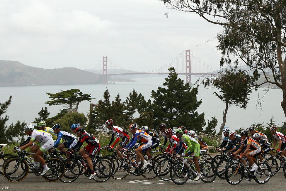 2012. május 14. A Tour of California országúti kerékpáros verseny mezőnye, háttérben a híd párás sziluettje. A hídon mellesleg jelenleg                          zajlik egy 390 millió dolláros felújítási és                         megerősítési projekt. A cél, hogy a földrengésveszélynek kitett, a                         Szent András törésvonal közelében fekvő építmény képes legyen                         átvészelni egy 8,3-as erejű, 90 másodperces rengést.