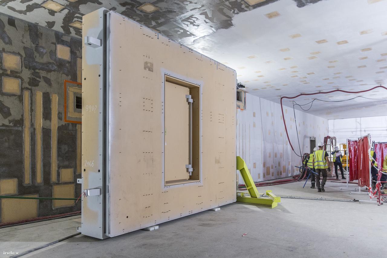Haladjunk tovább, nincs itt semmi látnivaló, ez csak egy ajtó. Egy 4,2 méter széles, 3,8 méter magas, 0,8 méter vastag üreges acélajtó, amit a helyszínen töltenek meg nukleáris minősítésű betonnal. Ezzel az eredetileg 30 tonnás szerkezet 60 tonnásra hízik. A tokamakot körülvevő portszobákat – ahol a diagnosztikai eszközök kapnak majd helyet – ilyen ajtók zárják el három szinten is. Ezek biztosítják, hogy a tokamakból ne juthasson ki neutronsugárzás illetve sugárszennyező por. A tokamaképület belsejében 46 ilyen ajtó veszi körül a fúziós reaktort.