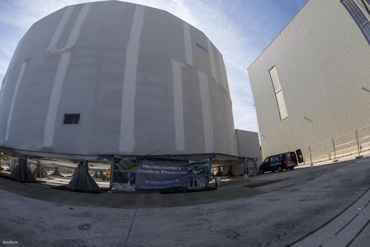 A kriosztátműhely mellett egy fehér zsugorfóliába gondosan becsomagolt, 30 méter átmérőjű gyűrűt látni jelenleg, aminek láttán azt lehetne gondolni, hogy a híres land-art csomagolóművész házaspár, Christo és Jeanne-Claude járt a telepen. A helyzet persze nem ez, a már elkészült kriosztátalkatrészt helyoptimalizálás miatt vitték ki a műhelyből a szabad ég alá, és hogy az időjárás viszontagságaitól megvédjék, egy ipari csomagolástechnikával foglalkozó holland cég, a Cocoon Holland BV burkolta be védőtakaróval.
