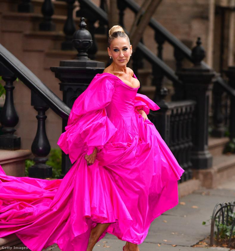 Itt éppen egy New York-i divatbemutatóra igyekszik ebben a hatalmas rózsaszínű ruhában, amin indokolatlanul sok a fodor, kivéve a dekoltázsánál, amiből majd' kibuggyannak Sarah Jessica Parker mellei.