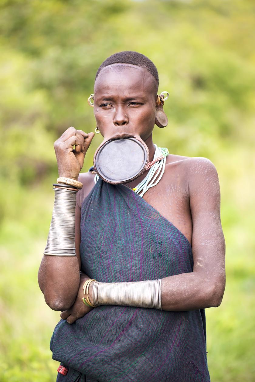 A hagyomány már a Kr. e. 9. évezredben is megjelent a források szerint, és azért alkalmazták, hogy elcsúfítsák a nőket, akik így kevésbé lettek vonzóak más törzsek, illetve később a rabszolga-kereskedők szemében.