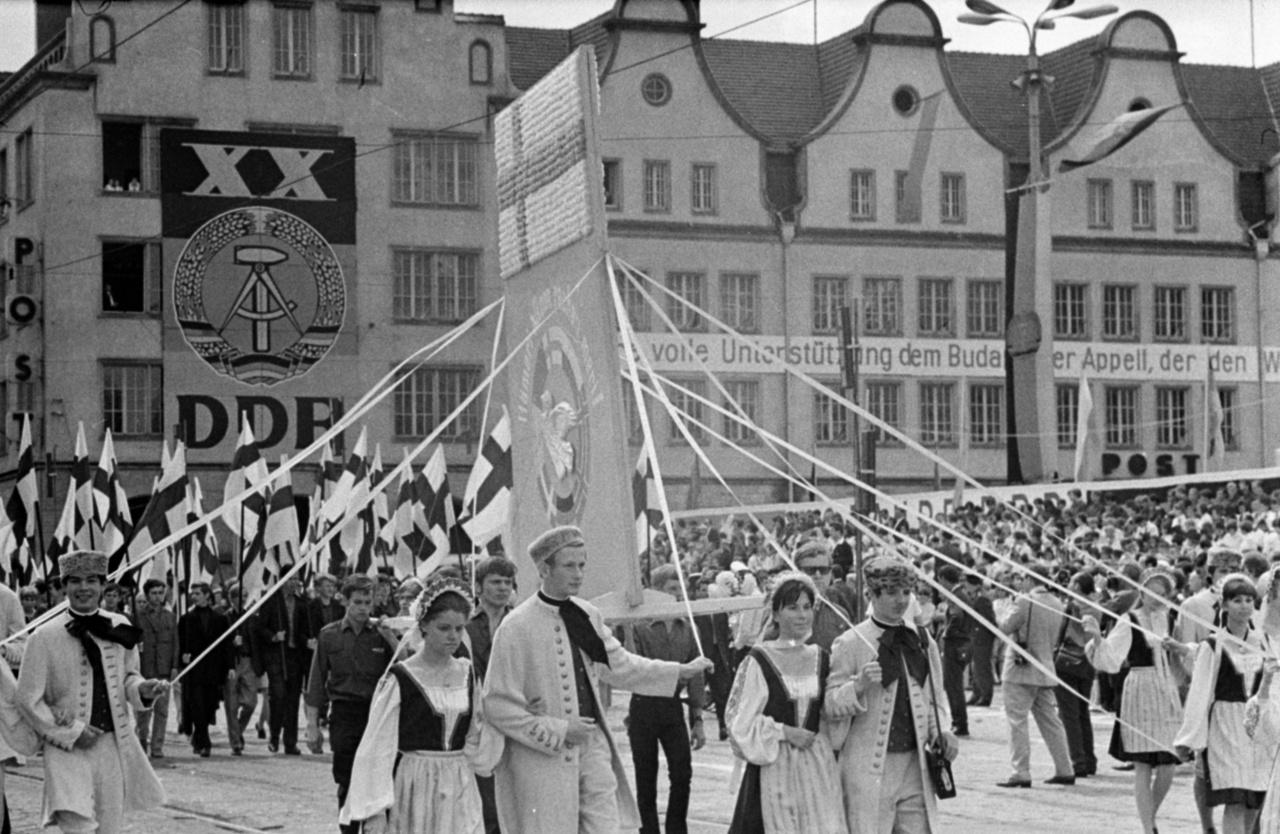 Utcai felvonulás az NDK megalapításának 20. évfordulóján. A háttérben olvasható a Budapest felirat, ami Varsói Szerződés Politikai Tanácskozó Testületének 1969. március 17-i budapesti ülésén elfogadott budapesti nyilatkozat támogatásáról szól. Ennek a dokumentumnak fontos szerepe volt a nyugati országok és a szocialista blokk közötti enyhülési folyamat elindításában.